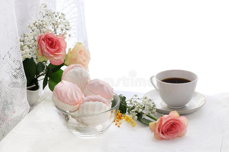 A cup of coffee and flowers on a light background, wishes of good morning and good day,. A cozy home stock images