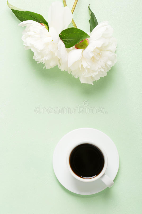 Cup of coffee and flowers peonies on light green table royalty free stock photo
