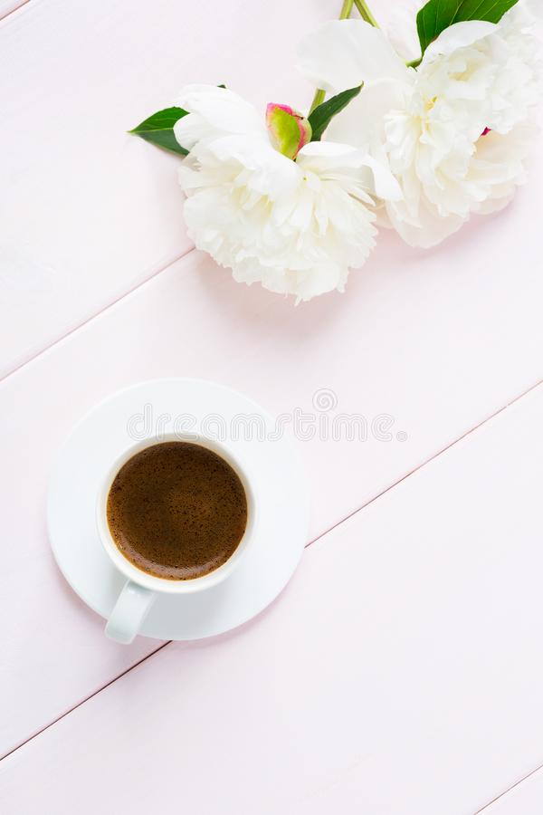 Cup of coffee and flowers peonies on light pink wooden table stock photography