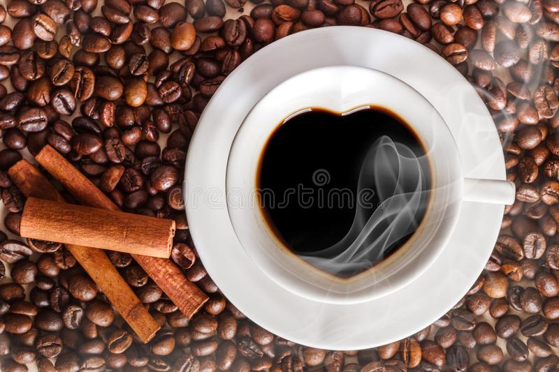 A cup of coffee in the form of heart with white smoke on the background of coffee beans close to the cinnamon sticks. Coffee with royalty free stock image