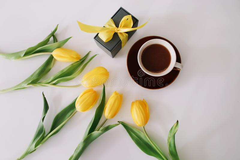 Cup of coffee, a gift box with ribbon and bouquet of yellow tulips isolated on white background. Flat lay, top view, copy space royalty free stock photos