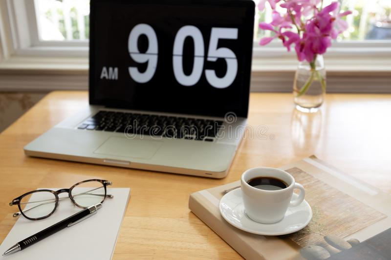 Cup of coffee with glasses and pen on wooden desk with laptop computer and flower. royalty free stock image