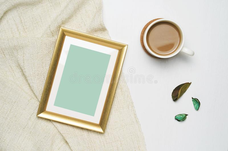 Cup of coffee and gold photo frame mock up on brown yarn and white wooden background. stock photography
