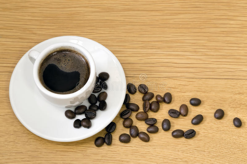 Cup of coffee and grain kopi luwak royalty free stock photos