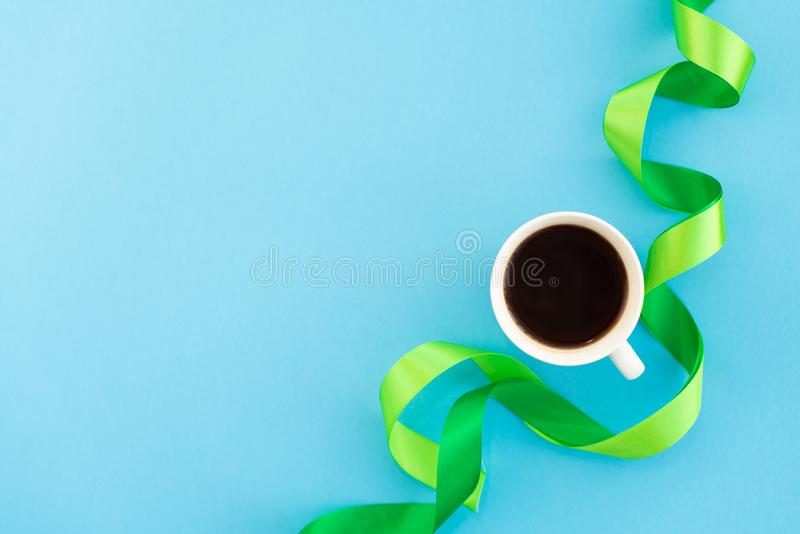 A cup of coffee with green silk ribbons on blue background. Design minimal concept. Mocup stock photography