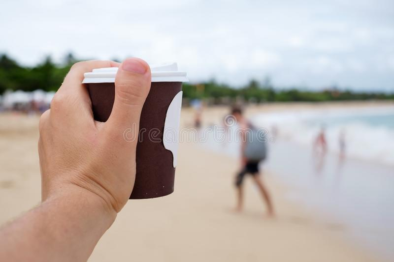 Cup with coffee in hand on background of blurred tropical beach stock photos