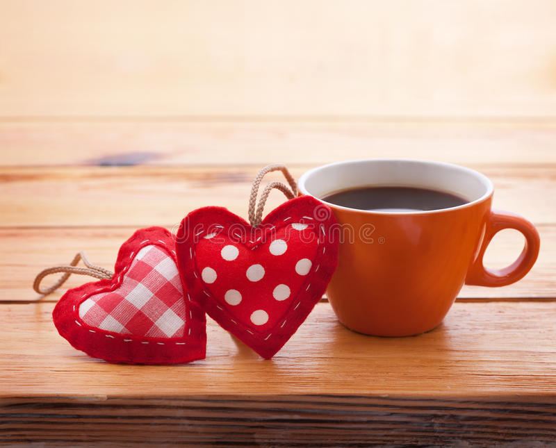 Cup of coffee and handmade heart fabric on wooden royalty free stock image