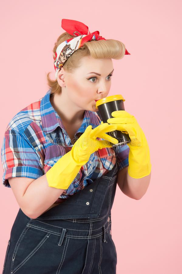 Cup of coffee in hands of girl with blonde curls. Pin-up style and craft cup of coffee. Woman drinks coffee in latex gloves royalty free stock photo