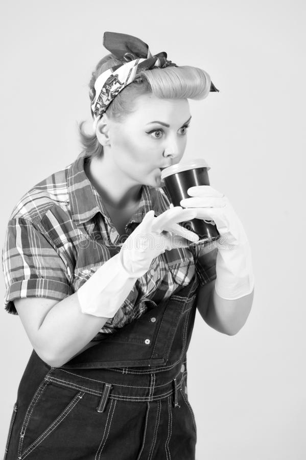 Cup of coffee in hands of girl with blonde curls. Pin-up style royalty free stock photos