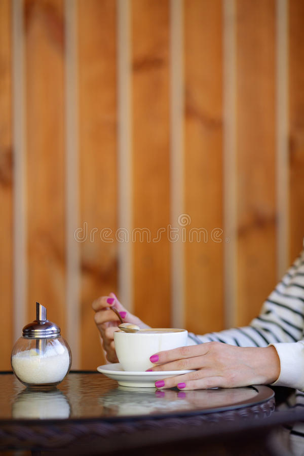 Cup of coffee in hands woman and sugar pot on table. Cup of coffee in hands of woman and sugar pot on round table stock images