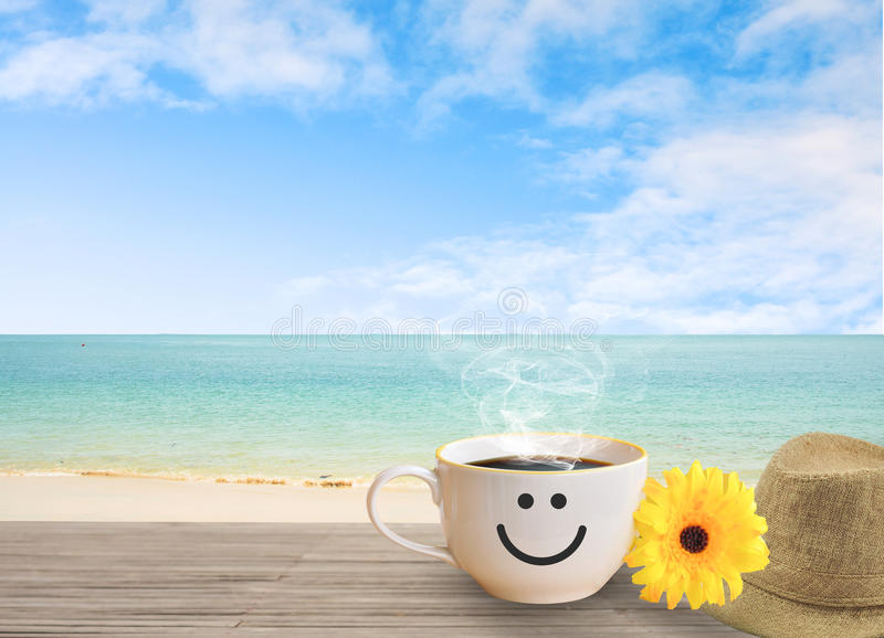 Cup of coffee with happy face on sand beach over blue sky. Cup of coffee with happy face on sand beach over blue sky and sea. concept relax travel in holiday royalty free stock photography