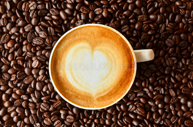 Cup of coffee with heart shape on coffee bean background stock photography