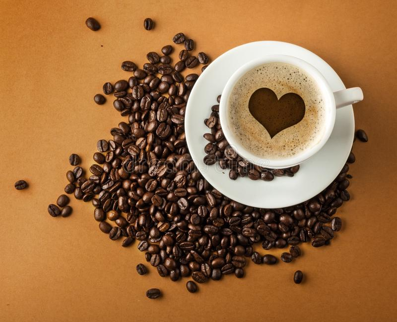 Cup of hot coffee with beans on paper background stock images