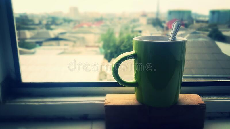 Cup of coffee on house window sill stock image