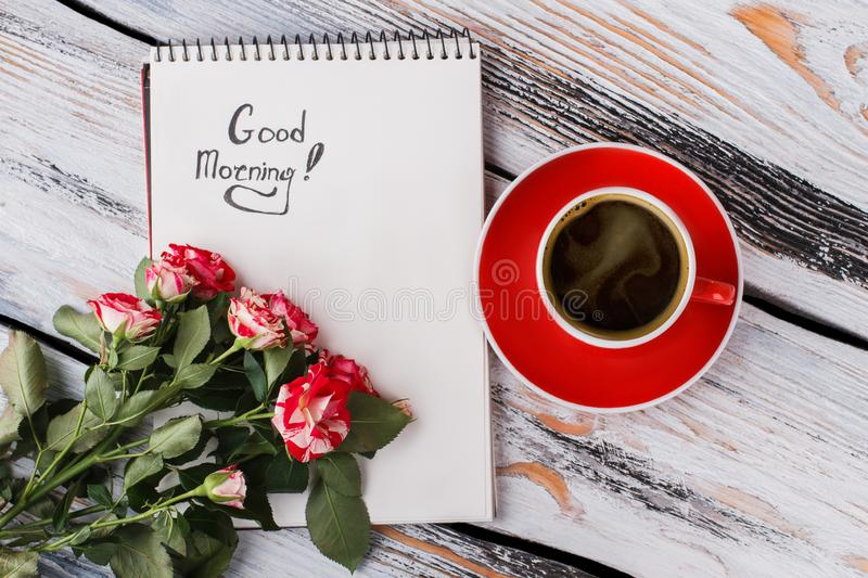 Cup of coffee, hybrid rose flowers and good morning note. Flat lay, top view. White wood background royalty free stock photos