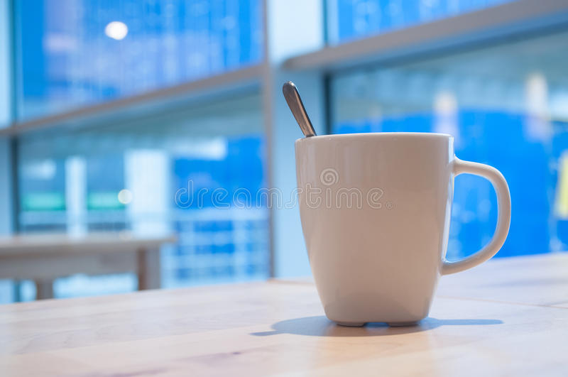 Cup of coffee in interior restaurant. Closeup of cup of coffee in interior restaurant royalty free stock image