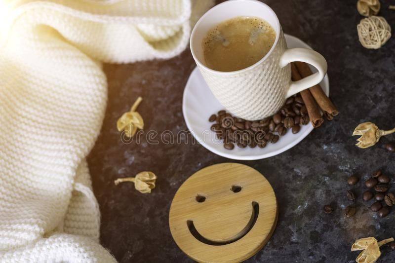 A cup of coffee is the key to a good mood. Wooden smiley on a dark, black, textural background. On the table there is a white, stock photo