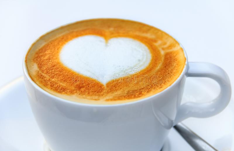 Cup of coffee with a latte art heart design at a cafe in Palma de Mallorca in Spain. Close up on a cup of a hot coffee with a latte art heart design at a cafe in royalty free stock image