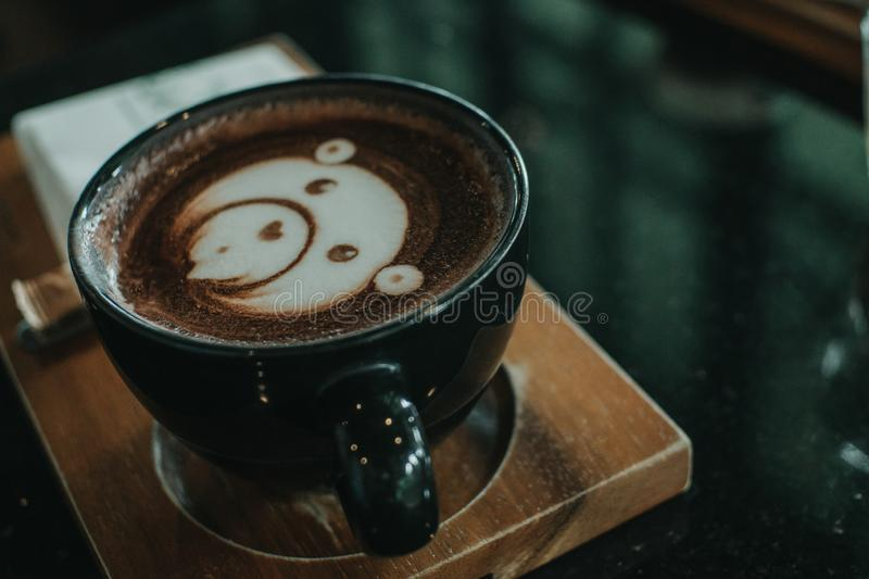 Cup of coffee latte and bear face bubble aet on wood table. A cup of coffee latte art on wood table  Cup of coffee latte and bear face bubble aet on wood table royalty free stock photo