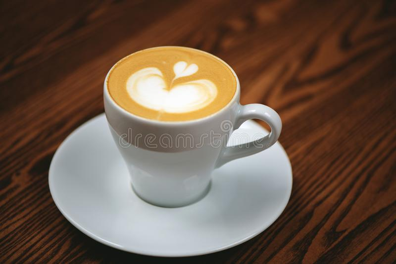 Cup of coffee with latte art on wooden background. stock photography