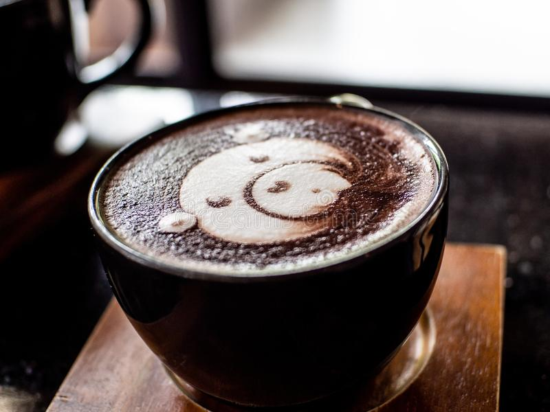 Cup of coffee latte and bear face bubble aet on wood table.  stock photos