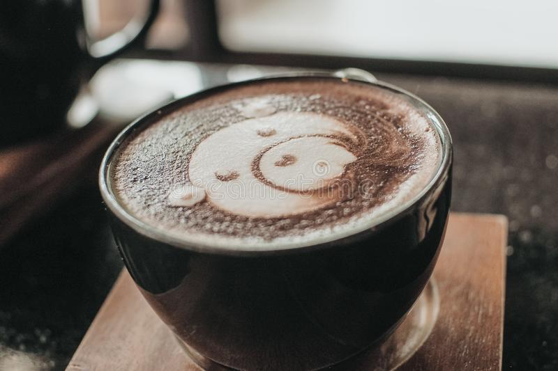 Cup of coffee latte and bear face bubble aet on wood table.  stock images