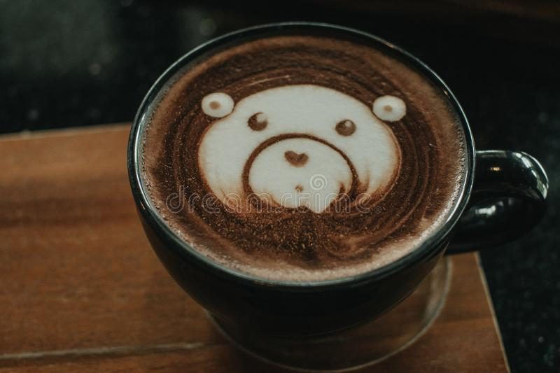 Cup of coffee latte and bear face bubble aet on wood table.  royalty free stock photo