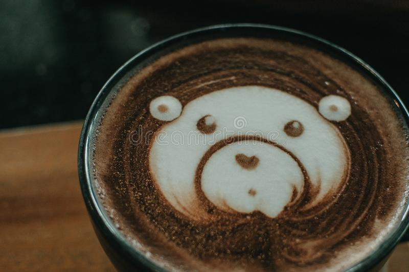 Cup of coffee latte and bear face bubble aet on wood table.  stock photography