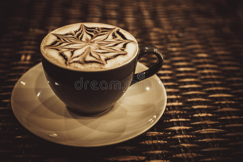 Cup of coffee latte with design art in froth, on a. Wooden table. Close up stock photos