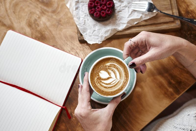 Cup of coffee latte on wooden table or background in woman hands from above. Having lunch in cafe. Opened notebook royalty free stock photography