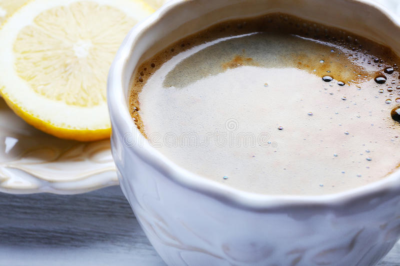 Cup of coffee and lemon slices on wooden table, close up royalty free stock photo