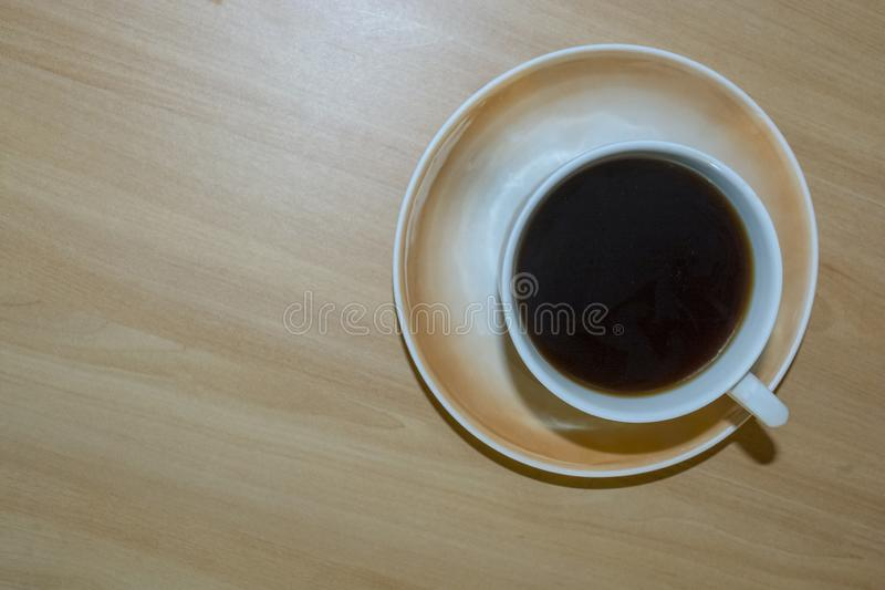A Cup of coffee on a light wooden table. royalty free stock photo