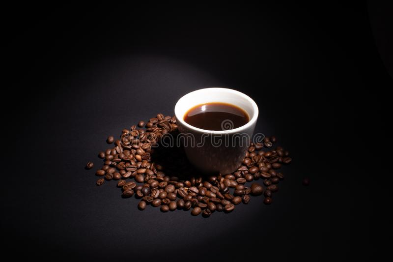 A cup of coffee is lit by a beam on the right above royalty free stock image