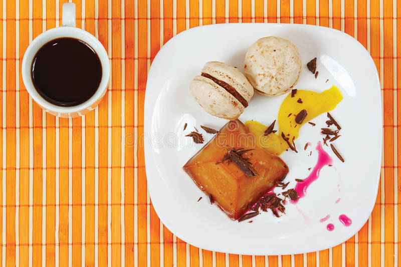 Cup of coffee, macaroons and caramel pudding stock image