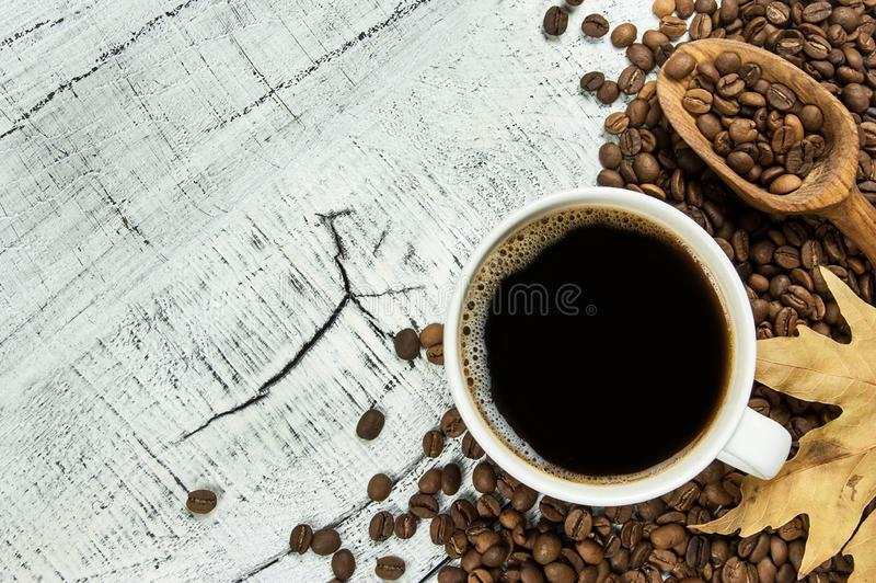 Cup of Coffee with many coffee beans and wooden shovel on white rustic and vintage wooden table with autumn leaf. Coffee backgrou stock photo