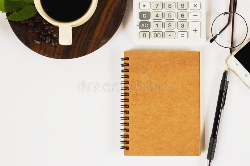 A cup of coffee with many objects on the working desk. A cup of fragrance coffee in the morning with many things there are a notebook , a pen , a calculator royalty free stock photos