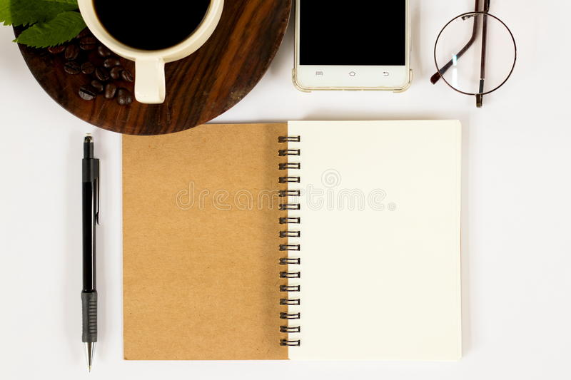 A cup of coffee with many objects on the working desk. A cup of fragrance coffee in the morning with many things there are a notebook , a pen , a calculator stock image