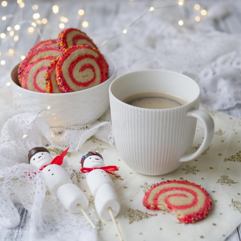 Cup of coffee with a marshmallow snowman and cookies in the form of a spiral in the Christmas table. Cozy winter breakfast. New Ye royalty free stock images