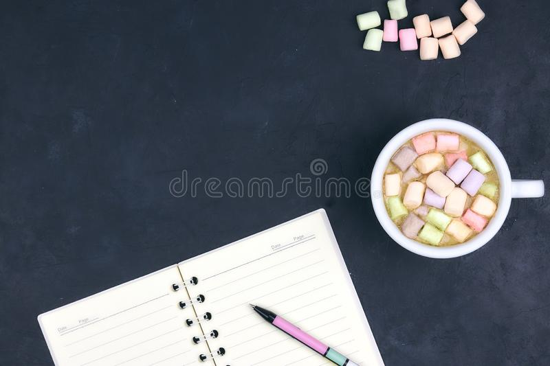 Cup with coffee and marshmallows, blank open notebook with pen on abstract black background. View from above. Flat layout. space royalty free stock photography
