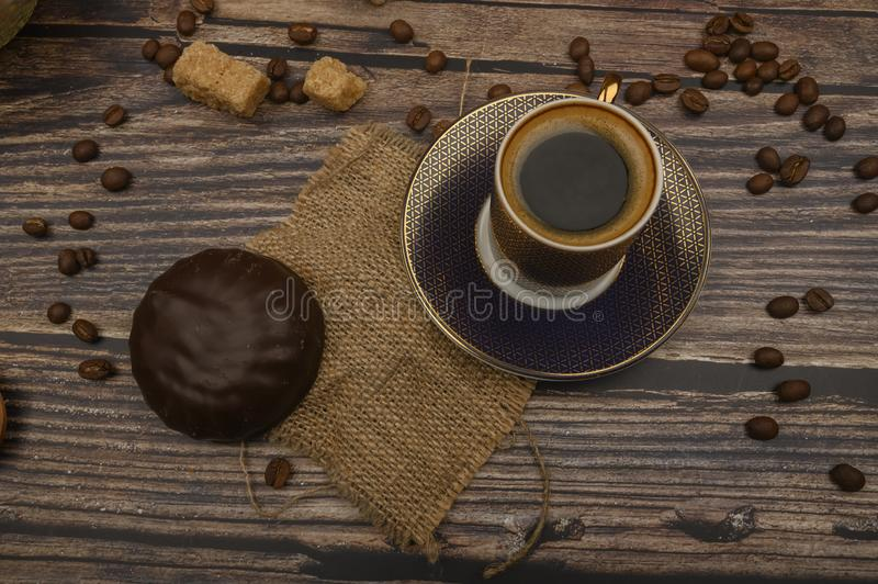 A Cup of coffee, marshmallows in chocolate, coffee beans, brown sugar on a wooden background. Close up stock photography