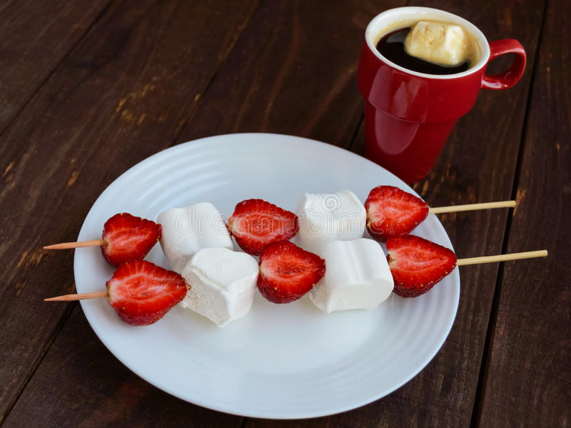 A cup of coffee and marshmallows with fresh strawberries on skewer. S on a wooden background royalty free stock photography