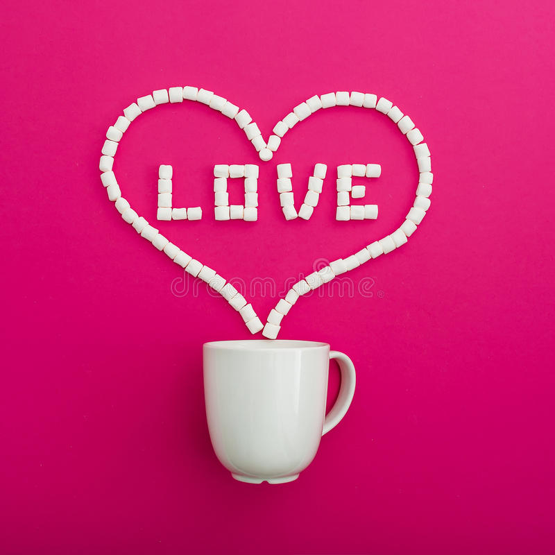 Cup of coffee and marshmallows on pink background. Heart symbol and quote Love. Flat lay. Top view stock images