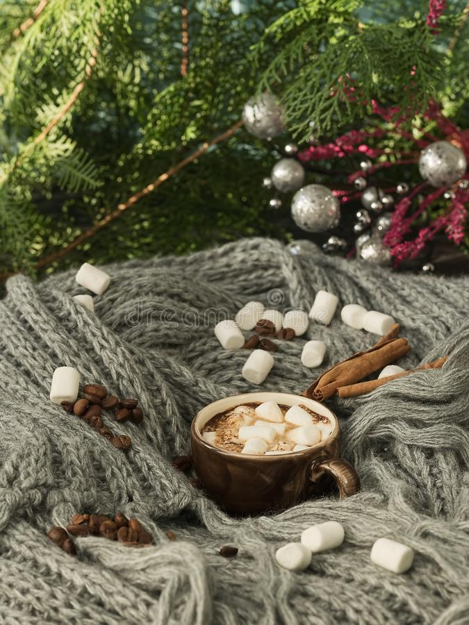 A cup of coffee with marshmallows on a woolen blanket, marshmallows and spices for the festive winter drinks are laid out around. royalty free stock photos