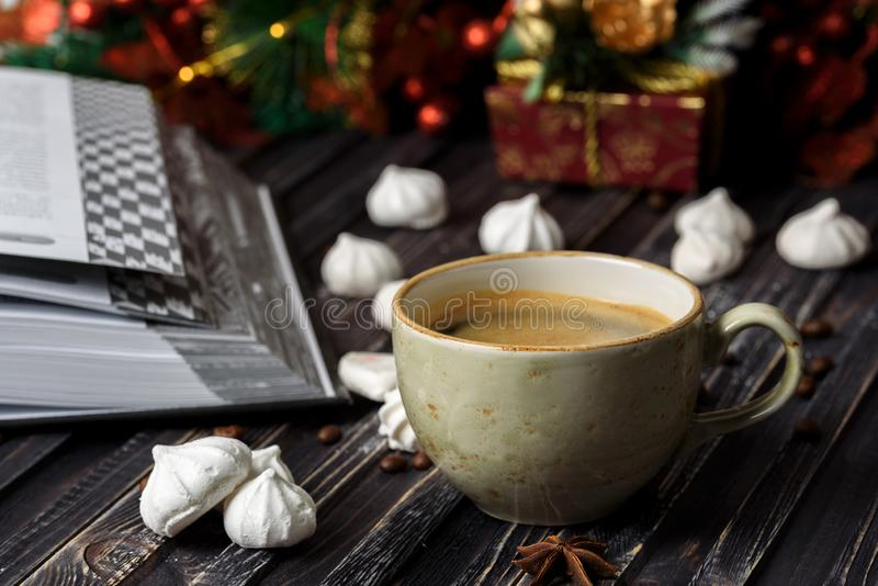 A cup of coffee with meringues and a book on a wooden background stock image