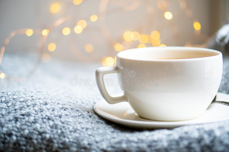 Cup of coffee with milk on cozy knitted winter blanket. Vintage style close-up stock photography