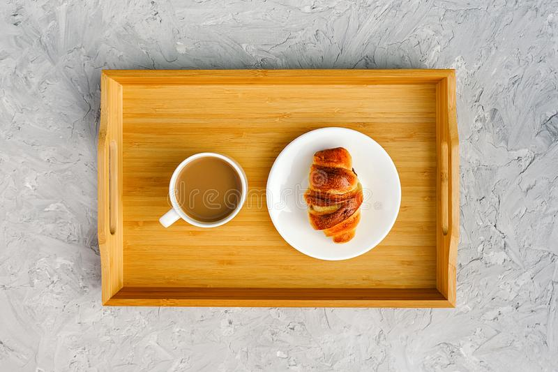 Cup of coffee with milk and freshly baked croissant on wooden tray on gray stone table. Concept Good morning Top view.  stock photo