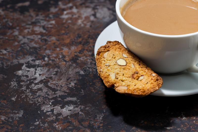 Cup of coffee with milk and Italian cookies cantucci on dark background royalty free stock image