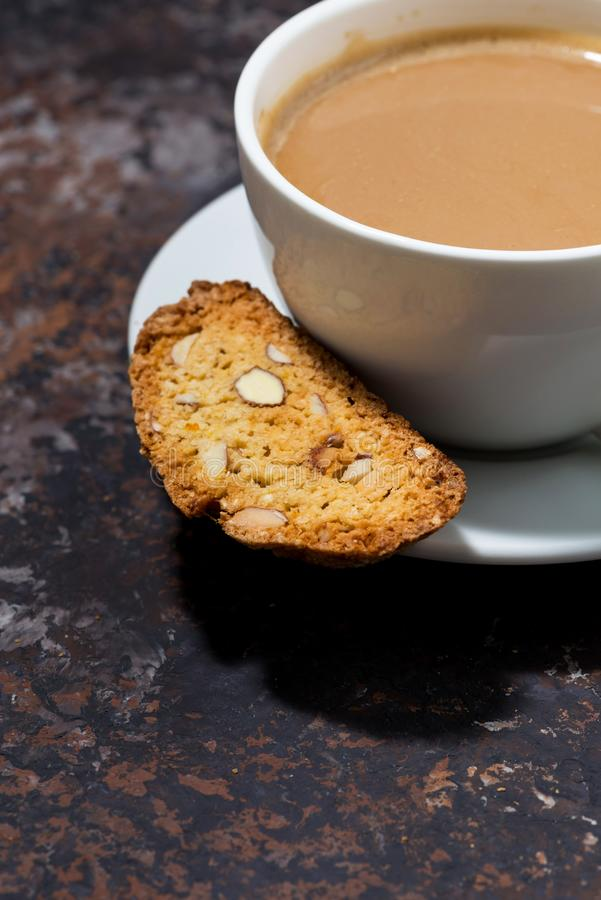 Cup of coffee with milk and Italian cookies cantucci on dark background, vertical royalty free stock images