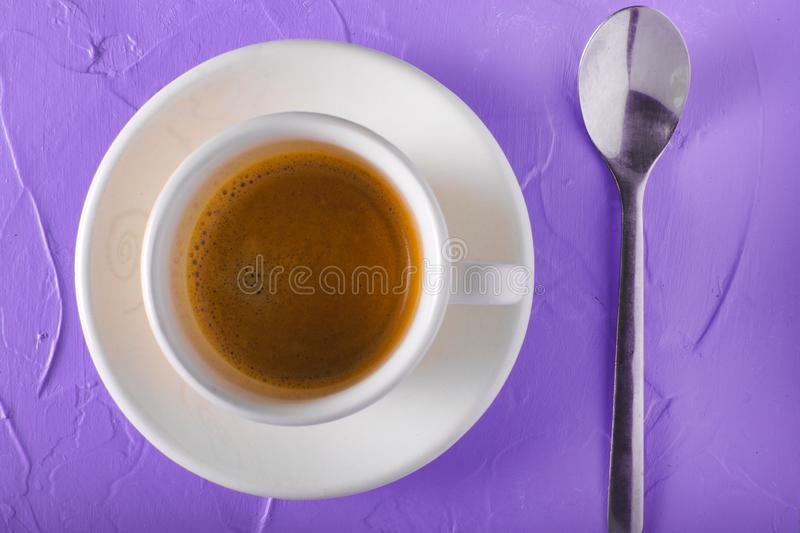 Cup of coffee with milk on a lilac royalty free stock photo