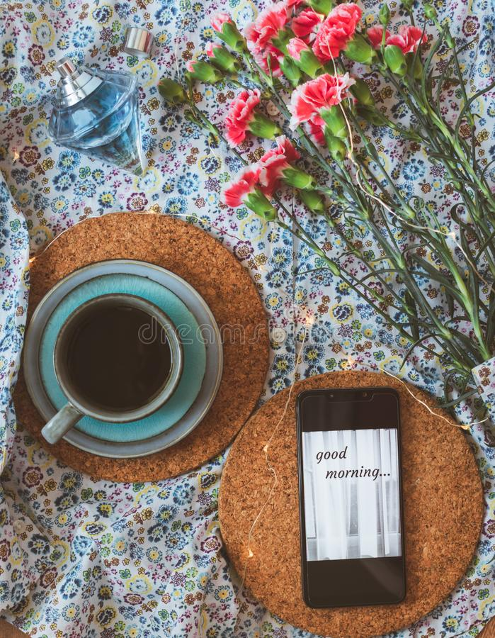 Cup of coffee, mobile phone with Good morning message and pink carnations on floral background. Flat lay or top view of a blue cup of coffee, mobile phone with royalty free stock photo